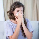woman sneezing into kleenex