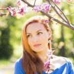 woman outside under cherry blossoms